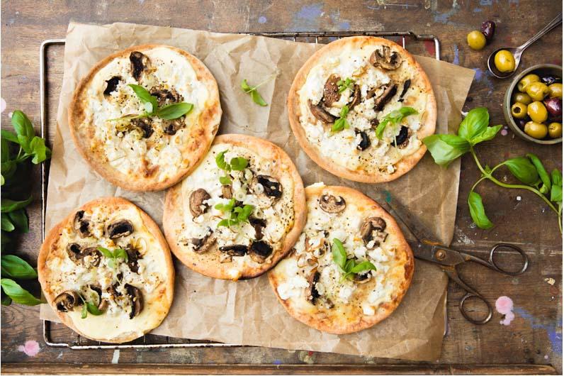 Goda små pizzor med salladslök, champinjoner och smulad fetaost.