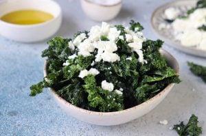 Grönkålschips i en vit skål med smulad feta