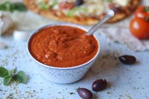 En skål med tomatpizzasås med en pizza i bakgrunden