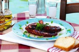Bläckfiskarmar i vinägersås på grekisk taverna, serverad med några glas ouzo